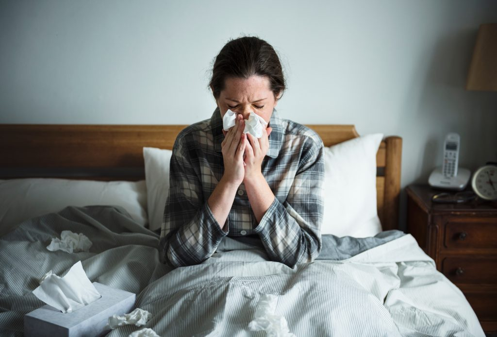 sick woman in bed with cold or flu or COVID